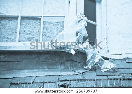 A window in an old house boarded up in blue tones - stock photo