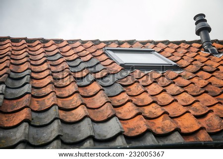 A window in the roof with red tiles and chimney - stock photo