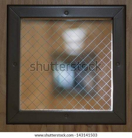 A window made of wire mesh glass, which is designed to resist breaking in a fire. - stock photo