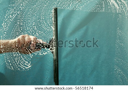 a window washer squeegiee cleans a window while window washing - stock photo