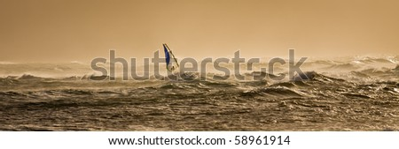 A windsurfer rides along the beautiful Maui's shores  a few minutes before sunset. - stock photo