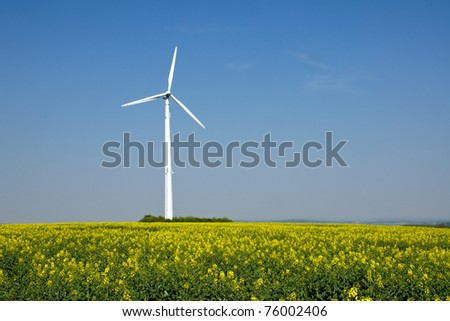 A windwheel and a field of rapeseed - stock photo