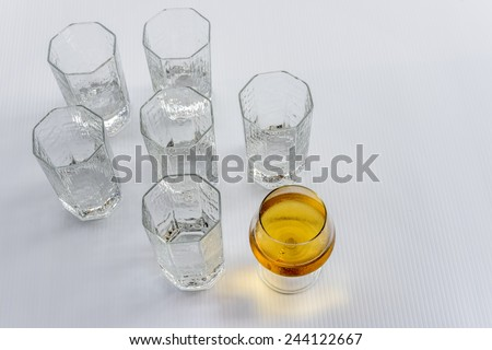 A wine glass with wine while others are empty water glass. Standout concept for those who lead with followers.  - stock photo