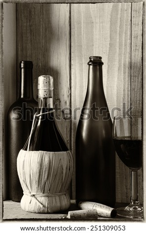 A wine still life with warm light from a window on the side. Three bottles, a wine glass and cork screw in a rustic setting, Vertical format. Vintage effect added. - stock photo