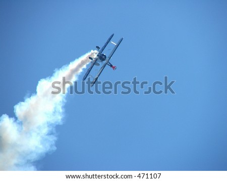 a wing walker making a shape with his hands while in flight - stock photo