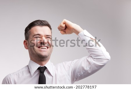 a winning man exulting and raising up his arm and fist because he is a successful one - stock photo