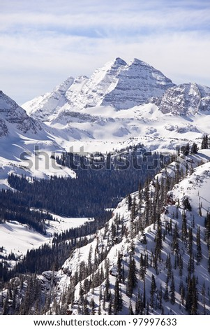 A winter landscape view, in vertical format, of the two peaks in the Maroon Bells massif in Colorado. - stock photo