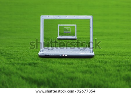 A wireless laptop on the green grass - stock photo