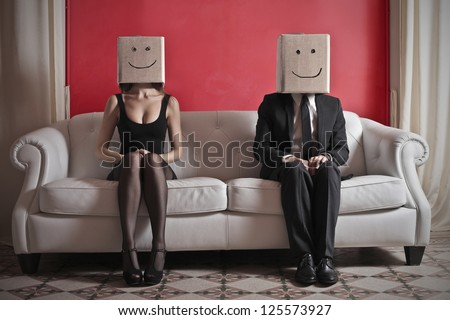 A woman and a man sitting on a sofa with a box on which is drawn a smile over their heads - stock photo