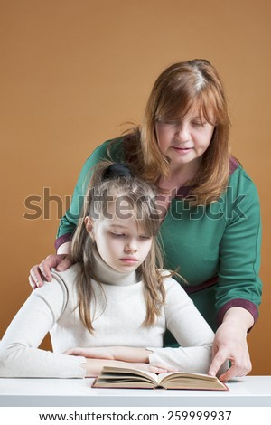 A woman and a ten-year girl reading a book.  - stock photo