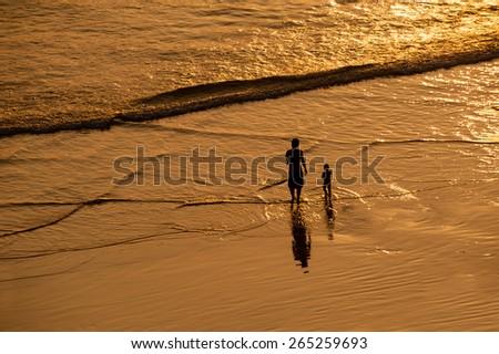 A woman and child walking along Varkala beach at sunset. - stock photo