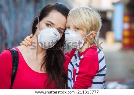 A woman and her son wearing protective face masks for pollution or virus. - stock photo