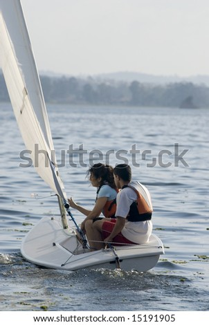 A woman and man are sitting inside a sailboat on the water.  They are looking away from the camera.  Vertically framed shot. - stock photo