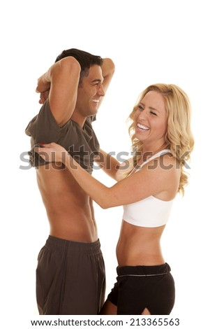 A woman and man laughing as she is trying to get his shirt off. - stock photo