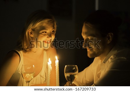 A woman and man share a joke over a glass of white wine at a candle lit table. - stock photo