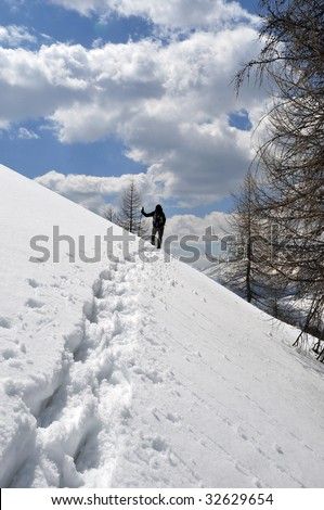 A woman ascend the mountain foot to the snowshoe - stock photo