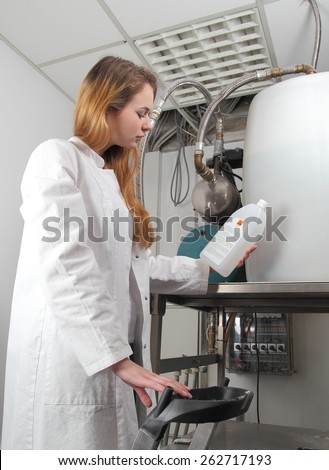 A Woman at a  plant with chemicals - stock photo