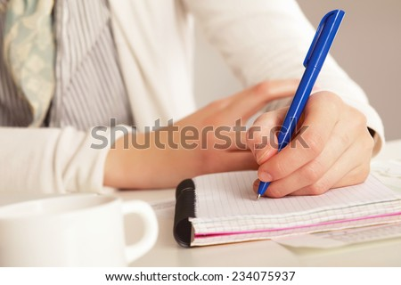A woman at the desk writting on a paper, isolated on white - stock photo