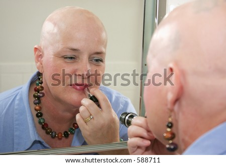 A woman bald from a health problem putting on makeup in the mirror. - stock photo