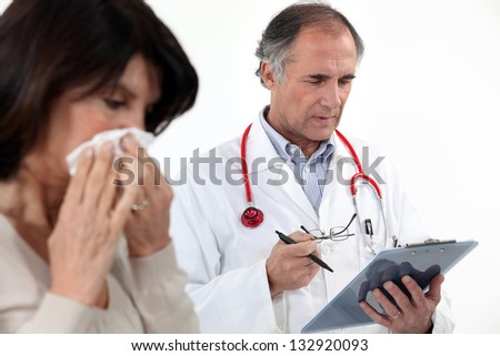 A woman blowing her nose at the doctor. - stock photo