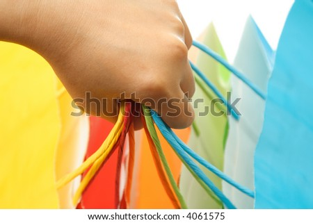 A woman carrying a bunch of colorful shopping bags - stock photo