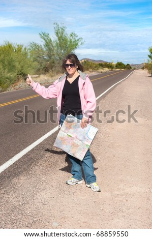 A woman carrying a map hitchhikes on a remote desert roadside. - stock photo