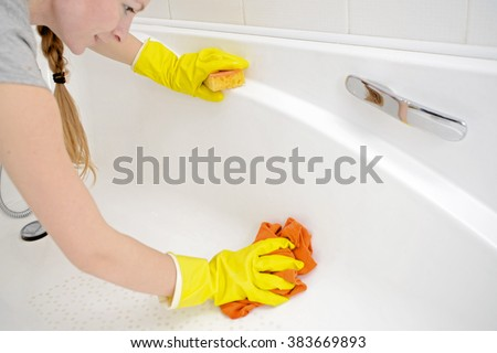 A woman cleaning bath at home. Female washing bathtub in yellow rubber gloves with orange sponge - housework, spring cleaning concept - stock photo