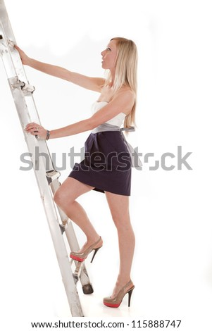 a woman climbing up the ladder in her heels and dress - stock photo