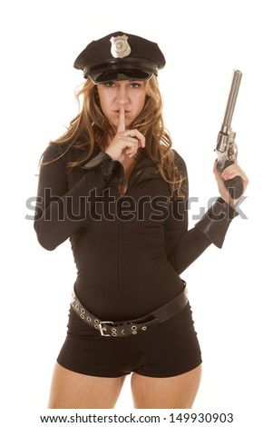 A woman cop holding up a gun with a finger to her lips. - stock photo