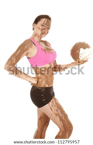 A woman covered in mud holding on to her volleyball covered in mud. - stock photo