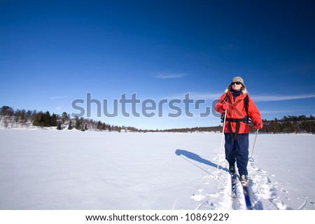 A woman cross country skiing across a frozen lake - stock photo
