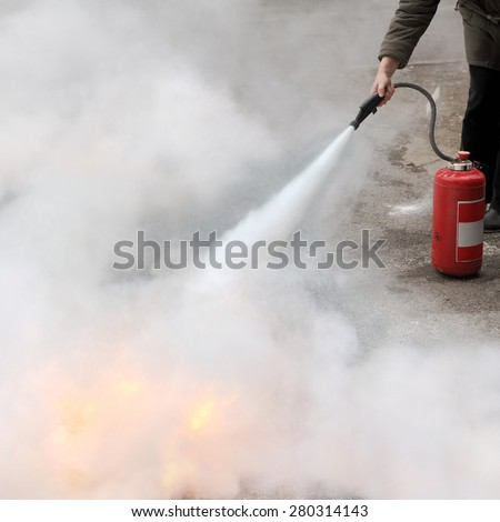 A woman demonstrating how to use a fire extinguisher - stock photo