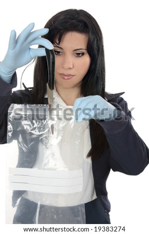 A woman detective collects a blood stained knife from a crime scene - stock photo