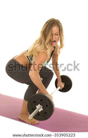 a woman doing a dead lift with a barbell. - stock photo