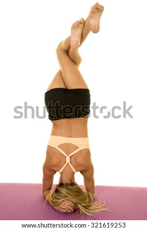 A woman doing a head stand with her legs twisted around each other. - stock photo