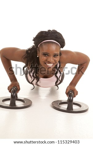 A woman doing a push up using push up bars. - stock photo