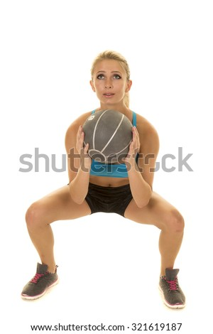 a woman doing a squat with a medicine ball. - stock photo