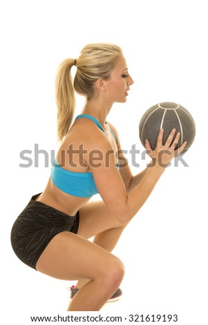 a woman doing a squat with a weighted ball. - stock photo