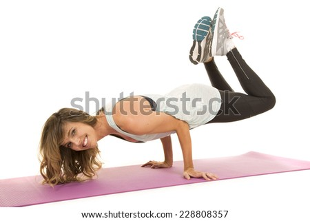 a woman doing a yoga pose, on her fitness mat. - stock photo
