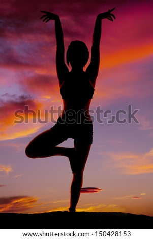 A woman doing yoga in the sunset silhouetted. - stock photo