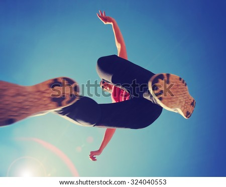 a woman dressed in active wear jumping directly over the camera with a wide angle lens during summer time with a lens flare in the corner - a unique perspective  - stock photo