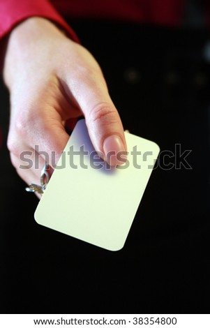 A woman dressed in office clothing holding out a blank business card. - stock photo
