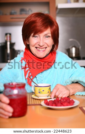 A woman drinking a cup of tea with raspberry - stock photo