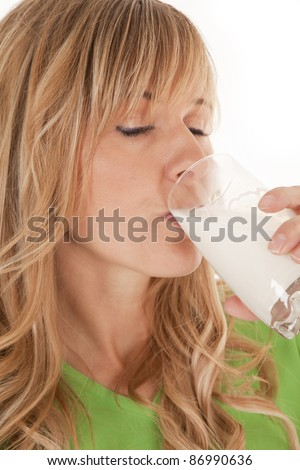A woman drinking a glass of milk with her eyes closed. - stock photo