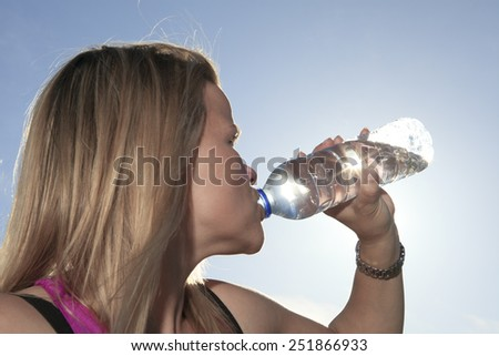 A woman drinking water outside with sky on the background. - stock photo