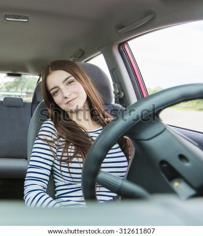 A Woman driver who is happy to have is new car - stock photo