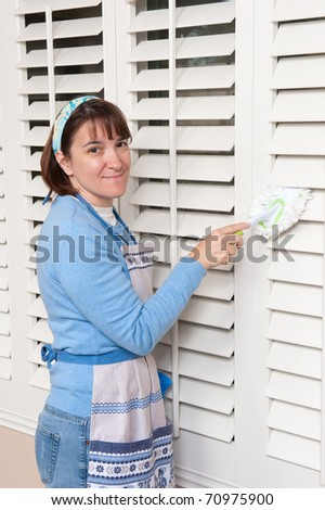 A woman dusts her window shutters while cleaning the house - stock photo