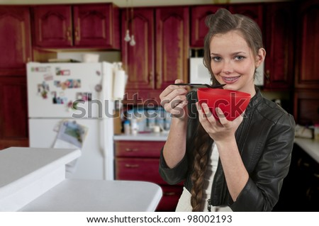 A woman eating food from a bowl - stock photo