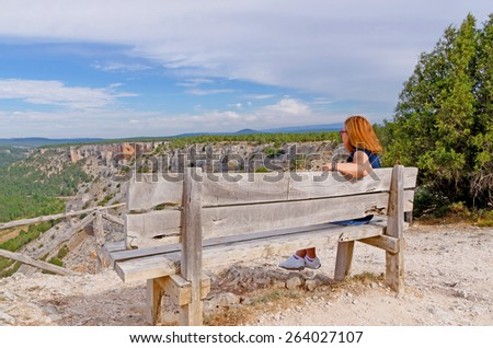 a woman enjoys the scenery sitting on a bench. Outdoors relax - stock photo
