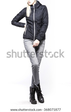 A woman(female, girl, model) wearing black jumper, grey pants(jeans, denim, trousers), black boots(walker) for winter close up isolated white at the studio. - stock photo